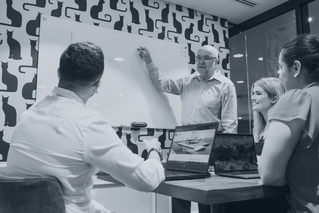 Facilitator explaining strategy model to small group leadership program